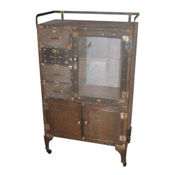 Pre-owned Vintage Steel Dental Cabinet On Wheels - 1950s dental cabinet of weathered steel is mounted on pivoting caster wheels. Four, steel, pull drawers line the left-hand side of the main compartment that is fronted by a glass-paneled door. Shelves can installed inside. The lower third of the cabinet consists of two compartments fronted by steel doors with a steel shelf within each compartment. The overall steel shell of the cabinet shows a surface rust patina that has been cleaned and sealed. The steel is solid as are all riveted joints. There is a towel bar on top wrapping three quarters around the cabinet. It is a lively piece with an unpretentious, versatile character. Maneuvers nicely on its wheels. Drawers and doors pull and swing neatly. Storage capacity is varied, accommodating small and larger items in kitchen, bath, living room. It has an inviting, lived-in quality that will quickly adapt to your living space like an old friend.