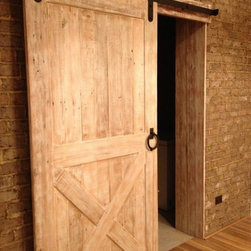 Barn Doors - This unique sliding barn door is made of hand-selected reclaimed Oak circa 1800s. The antique wood is character rich and retains its original nail holes, knot holes, checks and voids. Handcrafted in the stile and rail tradition, this door uses rabbit joint construction with inset vertical panels. In order to give this antique wood a modern look, the door was  painted white and then distressed.