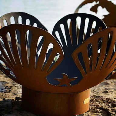"""Fire Pits - Great for Fall and Winter - The Barefoot Beach Fire Pit is reminiscent of playful days on a sandy beach this shell and starfish design takes us back to warm and sunny summer days. This original design is made to order by Tennessee craftsman in the heartland of America. They are constructed from heavy duty 1/4"""" thick mild carbon steel and are the most durable steel fire pit made anywhere. The inner bowl has a high temperature resistant coating and comes with a 1 1/2"""" diameter rain drain. The outer iron oxide patina is maintenance free and the fire pit can be left outside in all weather conditions. Over time and use the patina will mature and darken a few shades and then remain permanent forever. Each unique fire pit is individually numbered by the artist on an attached brass plaque."""