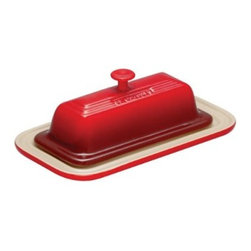 Le Creuset Butter Dish - Cherry - No table setting is complete without the butter dish, so make it the shining star of your place setting with the Le Creuset Butter Dish - Cherry. Crafted of stoneware so it will retain a cooler temperature longer, your butter will stay perfectly spreadable and no melted. Take it from fridge to microwave to dishwasher; this beauty can handle it all and come out gorgeous. It's cherry red enameled surface looks fantastic and is easy to clean, durable enough for daily use, and resists chipping and cracking. It even includes the signature Le Creuset triple-ring accent, smart handle, and 5-year manufacturer's warranty.About Le Creuset of America Inc.From its cast iron cookware to its teakettles and mugs, Le Creuset is a global standard of inimitable color and quality. Founded in 1925 in the northern French town of Fresnoy-Le-Grand, Le Creuset still produces enameled cast iron in its original foundry. Its signature color, Flame, was modeled after the intense orange hue of molten cast iron within a cauldron (or Creuset in French), and has been a Le Creuset bestseller from the company's first year to the present day.Though best known for its vibrantly colored cookware and original inventions such as the Dutch oven, Le Creuset has also forged a name as a creator of stoneware mugs and enamel-coated stainless steel teakettles. The style and performance of Le Creuset's Cafe Collection and tea accessories are rooted in classic French cookware: bold colors, cylindrical loop handles, unmatched thermal resistance and heat distribution, and of course the iconic Le Creuset three-ring accent. Through its consistent qualities of authenticity, originality, and innovation, Le Creuset maintains a connection to both heritage and modernity.