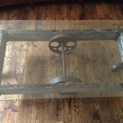 Rustically Modern Coffee Table - Vintage Industrial coffee table cart from early 1900-1950's. Unique Rail-Cart frame, along with Cast iron wheels and brackets. Brand new glass top, is