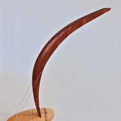 Peering Lamp - A modern lamp made of a mahogany curve perched atop a red oak base, the Peering Lamp is also an intriguing sculptural piece. The central curve is not attached to the base by any kind of fastener or adhesive, but is instead held firmly in place by the counteracting forces provided by the two cables that pass through it. With seemingly so little holding it in place, the curve leans forward and away from the base in a suggestion of imminent movement. The LEDs, though small, are very bright and allow the lamp to function well as a desktop task lamp.
