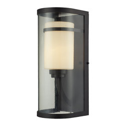 Elk Lighting - EL-14102/1 Caldwell 1-Light Outdoor Sconce in Oiled Bronze - This Indoor/Outdoor Collection has innovative styling for a clean, transitional appearance. The subtle textured clear outer glass surrounds the smaller opal white glass cylinder inside for added depth and character. The powered coated steel frame is finished in oiled bronze.