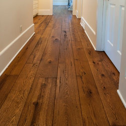 Reclaimed Wood Flooring - This gorgeous floor is made with Antique Resawn Oak materials. It has been finished with a stain, but maintains all of its original character marks, knot holes, grains and nail holes. Reclaimed wood in one-of-a-kind and unparalleled in its beauty.