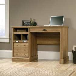 Sauder - Sauder Barrister Lane 1-Drawer Desk - Scribed Oak Multicolor - 414836 - Shop for Desks from Hayneedle.com! Traditional in inspiration but universal in appeal the Sauder Barrister Lane 1-Drawer Desk Scribed Oak features clean lines and versatile storage for home or office including a full-extension bottom drawer for letter or legal-size hanging files. Cup pull hardware card label holders and a decorative six-knobbed drawer front enhance the period-style appeal of this high-density particleboard desk which is covered by Sauder with a five-year limited warranty.About SauderSauder is North America's leading producer of ready-to-assemble (RTA) furniture and the nation's fifth largest residential furniture manufacturer. Based in Archbold Ohio Sauder also sources furniture from a network of quality global partners including a line of office chairs that complement its residential and light commercial office furniture. Sauder markets more than 30 distinct furniture collections in a full line of RTA furnishings for the home entertainment home office bedroom kitchen and storage.Sauder is a privately held third-generation family-run business. The company prides itself on its awareness that all function and no fashion makes for a dull living space when it comes to home furnishing products. That's why Sauder's award-winning design team has produced more than 25 collections of stylish furniture that span the design spectrum. From minimalist modern or contemporary to classic 18th century or country styles Sauder has what you're looking for. The company offers more than 500 items - most priced below $500 - that have won national design awards and generated thousands of letters of gratitude from satisfied consumers.