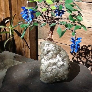 Wisteria Glass Bonsai - The blue glass flowers dangle from the copper thread of the copper tree filled with green glass leaves.  Anchored to a green rock that sits on a slate base.  This tree has a unique and one of a kind look.