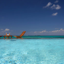 Murals Your Way - Palmenstrand 4 Wall Art - A pair of lounge chairs await in the shallow water off a tropical island under a blue sky