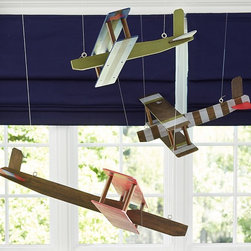 Wood Hanging Biplane - These wooden airplanes add visual interest to an often neglected area of a room — the ceiling! I can bet that any boy, young or old, would love to fall asleep looking up at a set of these vintage-inspired airplanes.