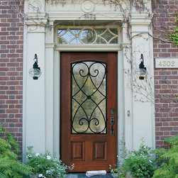GlassCraft's Premium Fiberglass Arch Lite Door with Charleston wrought iron - This Southern style brick home influenced by Colonial Revival architecture is perfectly matched by GlassCraft Door's Premium Fiberglass-Estate Collection door with Arch Lite and Charleston wrought iron grille. This door features a beautiful Cherry wood grain in Sycamore finish. A variety of different wood grains and color finishes are also available.