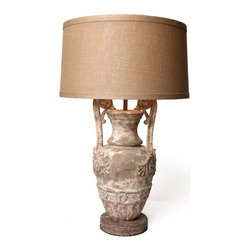 Helena Urn Lamp - A stunningly and intricately carved stone-like urn sits atop a round etched base with the urn being accented with reedy handles finished off with quaint goose-like heads resting atop the vase. The texture and finish of the Helena Urn Lamp adds country charm to an otherwise very formal shape presentation, set off by an ecru linen shade.