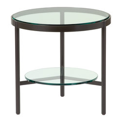 Thomas Pheasant Outdoor Round Side Table: TP-525 - The Round Side Table features a top of clear tempered glass with flat polished edges designed to fit tightly within its aluminum frame, supported by three legs. A floating glass shelf provides additional space and a graphic quality. The architectural simplicity of this table enables flexibility in many settings.