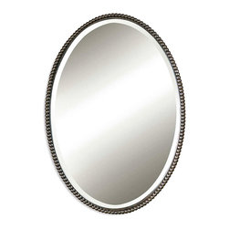 Sherise Bronze Oval Mirror - In the Sherise Bronze Oval Mirror, one may catch the reflection of a shimmering midday sun, a sliver of silver moon, a posy of blooms peeking out from a vase, or  the winsome smile of someone dear. The mirror boasts a glimmering frame of hand-forged metal in lightly distressed, oil rubbed bronze with a decorative beading design; a generous bevel suggests old-world glamour.