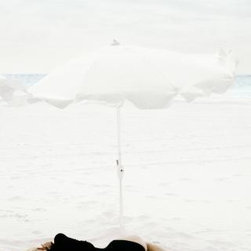 """""""Kirsty Hume Harbor Island"""" by Pamela Hanson - The white sand, oversized umbrella, cloud-filled sky, and ivory-colored towel merge into the picture-perfect paradise of Harbour Island. Communicating a meditative vibe, the photograph takes its viewer to a breathtaking vacation destination. The model, Kirsty Hume, lays delicately on the sand in her stylish bathing suit, the fashion model motif sneaking its way into the otherwise cohesive natural world."""