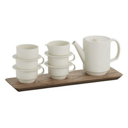 Ralli Tea Set - London-based Ralli Designs has created an exclusive tea set that marries pure, functional design with eye toward practicality. Crafted in England of cream-colored ceramic, the ingeniously shaped pieces stack easily for space-saving storage. Cups are recessed to fit snuggly into bowls, which can serve desserts or serve as saucers. Creamer, sugar bowl and teapot feature the same design, which fits neatly into recessed wood tray for serving and can also be stacked.