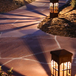 Attraction Lights overview - Lantern Grande Beacons and Mini Bollards (at driveway) natural rust finish.  Recommended LED lamps produce interesting shadows on flagstone walkway.  Photo by Lyle Braund