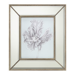 Silvery Blue Tulips III Print with Mirrored Frame - Influenced by the luxurious botanical prints gracing the garden rooms of English country manses, the artwork presents a quiet blue background that introduces an intricate illustration of a magnificent bloom with delicate petals and stem rendered in whispers of gray. The wide mirrored frame accented with petite beading in the bevel and each corner lends a touch of refined glamour to the Silvery Blue Tulips III artwork.