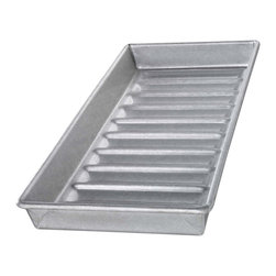 USA Pans New England Hot Dog Bun Pan - The USA Pan New England Hot Dog Bun Pan has been designed with many of the same standard features of industrial baking pans. Each pan is constructed of aluminized steel the material of choice for commercial bakeries. Metal thicknesses have been selected that allow even heat distribution and maximum service life. Our pans also use steel wires in the rim construction of most pans to provide additional strength and resist warping. Each pan is coated with AMERICOAT© Plus a proprietary silicone coating that nearly all North American bakers prefer over dark non-stick coatings. AMERICOAT© Plus is a clear non-stick environmentally friendly coating that is specifically formulated for superior baking and does not contain any PTFE's or PFOA's.USA Pan bakeware features a corrugated or fluted design. The corrugation maximizes pan strength and prevents warping denting and other effects of everyday use. Corrugation also minimizes surface contact with baked goods which translates into an evenly baked product that is easily released. USA Pan has been developed by the world's largest manufacturer of industrial bakeware and has been providing the world's leading commercial bakeries with the highest quality baking pans for over 50 years. When you purchase a USA Pan you are buying products that meet industrial standards for innovation quality and durability. Put simply our pans are the best available and are proudly produced in the UNITED STATES OF AMERICA.