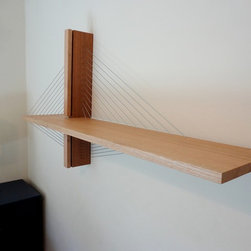 Suspension Shelf - This suspension bridge-inspired shelf is a great modern addition to any room. A sculptural piece in its own right, the shelf is especially great for those who want to be economical with their floor space. A vertical mahogany fin mounts to the wall while the red oak shelf floats one inch out. The shelf is cantilevered out from the mahogany fin with steel cables that bear the load of books and other items while at the same time creating beautiful contours. The piece is available with the shelf on either the right (as pictured) or the left (mirror of pictured version) of the mahogany fin.