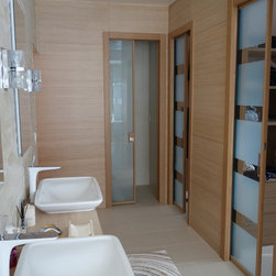 Modern Bath Solutions - Modern style glass pocket doors into the walk-in-closets and toilet rooms