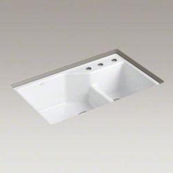 "Kohler - Kohler K-6411-3-0 White Indio Indio 33"" Double Basin Undermount - Product Features:  Double basin sink with a 70/30 split provides increased versatility for any task Covered under Kohler s limited lifetime warranty The large/medium basins allow you to keep clean and dirty dishes separate, while providing ample room for oversized pots and pans Two bottom basin racks, a colander, and a walnut cutting board are included and custom-fit to work perfectly with the sink Constructed of enameled cast-iron which combines strength, durability and insulation benefits Undermount installation gives an integrated graceful look to the sink Offset drain location increases workspace area in the sink as well as storage area underneath All hardware needed for installation included  Product Technologies / Benefits:  Enameled Cast-Iron:  Kohler Enameled Cast-Iron combines the strength, durability, and insulation benefits of cast-iron with the scratch, chip, and burn resistance of a baked, powder coat finish and comes with an exceptional Lifetime Limited Warranty. When these materials are combined it gives the sink or tub the strength to last a lifetime of use. Kohler Enameled Cast-Iron is also available in a wide variety of specialty colors allowing you to truly customize your home. Smart Divide:  The basin divider is set to a lower height than perimeter of the sink; you gain the convenience of a single basin sink completely filled, without losing the functionality of a double basin sink. The lower divider also gives more room for working with larger pots and pans providing more access for filling and cleaning.  Product Specifications:  Height: 9-3/4"" (measured from the bottom of the sink to the top of the rim) Overall Width: 21-1/8"" (measured from the back outer rim to the front outer rim) Overal"