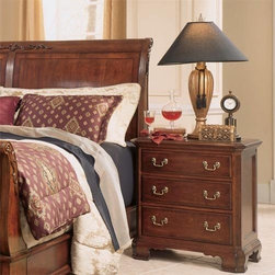 "Cherry Grove Small Nightstand - Handsome and refined. Complete your traditional bedroom set with the Cherry Grove Nightstand. The warm cherry wood color adds distinction and a cozy atmosphere to the room.The scalloped bottom and swinging brushed-bronze drawer handles provide decorative design for this nightstand. The side panels are recessed for extra detail. With three easy-open drawers this piece will be a useful accent in your home.For a nightstand to love for a lifetime place your order for the Cherry Grove Nightstand today.About American DrewFounded in 1927 American Drew is a well-established leading manufacturer of medium- to upper-medium-priced bedroom dining room and occasional furniture. American Drew's product collections cover a broad variety of style categories including traditional transitional and contemporary. Their collections range from the legendary 18th-century traditional """"Cherry Grove """" celebrating its 42nd year of success to the extremely popular """"Bob Mackie Home Collection """" influenced by the world-renowned fashion designer Bob Mackie. """"Jessica McClintock Home"""" features another beloved designer bringing unique style to an American Drew line. American Drew's headquarters are located in Greensboro N.C. Their products are distributed through thousands of independently owned retailers throughout the United States and Canada and around the world."