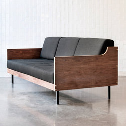 Gus* Modern Archive Sofa - Sleek and dramatic, the Archive Sofa is a box-framed design with a strong Mid-Century influence. Walnut-finished, exposed py on all sides makes it an ideal choice for open-concept spaces.  It features a blind-tufted seat, powder-coated cylindrical steel legs, and exposed brass fittings.  The back cushions can be removed to convert the sofa into a daybed, for relaxing or to accomodate overnight guests.  The inner frame is constructed with kiln-dried, 100% FSC®-Certified hardwood, in support of responsible forest management.