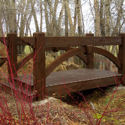 McLellen Timber Frame Bridge - Timber frame bridge kit installed over a seasonally dry irrigation creek bed.