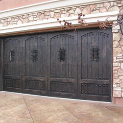 Ranch House Doors - Knotty Alder Stain Custom Wood Door with Speakeasy Deco Grilles - This door is one of two on the property.  They are 16*8 & 8*8 wood carriage doors with speak easies and clavos.  They are stained so that they look rustic.  The house is a modern spanish style and these doors really make a big architectural statement.  The hardware is incredible and really compliments the garage door.  This is one of our most popular wood doors.  Photo credit: Agi Dyer