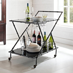 Powell - Powell Serving Cart - Gunmetal Gray Multicolor - 532-415 - Shop for Carts from Hayneedle.com! Get the party started by wheeling out the Powell Serving Cart - Gunmetal Gray. This handsome serving cart features a metal frame with bamboo-detailed ornamentation and tempered black glass shelves. Two trays provide plenty of room for holding bottles glasses shakers appetizer plates and more. A built-in bottle rack and glass holder on the bottom tray keeps the good stuff at a glance while antique caster wheels allow for smooth gliding across your entire house from the first guest s arrival to the last drop that leaves the glass.More About Powell FurnitureBased in Culver City Calif. the Powell company designs imports and distributes occasional dining accent and youth furniture across all style categories. Since 1968 Powell has grown to become one of the most recognized names in the home furniture industry. From sturdy safe childrens furniture to elegant bedroom and other home collections Powell continues to develop new and exciting designs for homes around the globe.