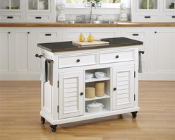HomeStyles - Brushed White Kitchen Cart - Inspired by the fusion of British colonial and old world tropical design, the Bermuda Kitchen Cart highlights poplar solids and engineered wood in a designer visible brushed stroke white finish. Further inspiration cab be found in the shutter style designed doors and intricate details. Bounteous storage is provided with two cabinet doors with one adjustable shelf behind each door, three adjustable shelves in middle, and two storage drawers. Other features include 7mm thick uniquely antiqued stainless steel top to complement the matching hardware, two towel bars, and industrial sized casters (two locking). Beautifully accented with antique brass hardware. 44.5 in. W x 17.75 in. D x 32 in. H