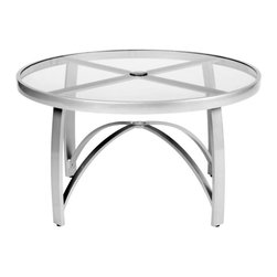 Woodard - Woodard Wyatt Flex 36 in. Round Coffee Table with Umbrella Hole - 564637 - Shop for Tables from Hayneedle.com! Whether you want to keep snacks and drinks handy for your guests or serve an informal lunch you'll be hard pressed to find a better option than the Woodard Wyatt Flex 36 in. Round Coffee Table with Umbrella Hole. Boasting clean lines and a contemporary design this coffee table-height piece is perfect for pairing with Wyatt Flex lounge chairs to create a cozy place to catch up with friends. It also does double duty as a dining table - simply pull the chairs up to the table and it makes a perfect spot for entertaining.Sturdily constructed of fully welded aluminum this table sports a smoked glass table top with an umbrella hole so you can sit in the shade on particularly hot days. Available in a choice of powder-coated finishes it will easily coordinate with your existing patio furniture and will not rust peel or blister even after years of use. What's more it is virtually maintenance-free and easily hoses off to clean. Made by Woodard the leader in quality patio furniture for 140 years this chat table offers a perfect blend of upscale elegance and lasting function.Important NoticeThis item is custom-made to order which means production begins immediately upon receipt of each order. Because of this cancellations must be made via telephone to 1-800-351-5699 within 24 hours of order placement. Emails are not currently acceptable forms of cancellation. Thank you for your consideration in this matter.For over 140 years Woodard craftsmen have designed and manufactured products loyal to the timeless art of quality furniture construction. Using the age-old art of hand-forming and the latest in high-tech manufacturing Woodard remains committed to creating products that will provide years of enjoyment.Superior Materials for Lasting DurabilityIn the Aluminum Collections Woodard's trademark for excellence begins with a core of seamless virgin aluminum: the heav