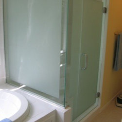 Framless Return Shower Doors with Knee Walls - Custom sandblast design to make the door and inline panel look like one pattern. We took the width of the sill and made a border on the perimeter and sandblasted the middle to give the whole enclosure a framed look. The 90 degree corner is secured with a over the top 90 degree sleeve so it does not interfere with the custom design of the enclosure.