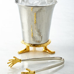 """Michael Aram - Footed Ice Bucket & Cold Hands Ice Tongs - SILVER - Michael AramFooted Ice Bucket & Cold Hands Ice TongsDetailsFrom the 25th Anniversary Commemorative Collection.Handcrafted of stainless steel 24-kt gold-plated metal and nickel-plated metal.Hand wash.Two-piece set. Ice bucket 6""""Dia. x 7.5""""T; tongs 7.75""""L.Imported.Designer About Michael Aram:American artist Michael Aram studied art in New York in the late 1980s before traveling to India on an inspirational journey where he discovered a rich metalworking tradition that inspired his turn toward handcrafted design. Michael Aram established a home and workshop in New Delhi where he began crafting objects ranging from tableware to furniture all of which reflect the hand of the artisan. The tension of line form and meaning is a distinguishing characteristic of Aram's extraordinary designs inspiring thoughtful appreciation and bringing a sense of ceremony in their day-to-day use. Each Michael Aram piece is handmade so no two items are exactly alike."""