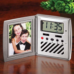 "Exposures - Home Sounds Clock Frame - Wake to your loved ones voices or an alarm with this beautiful silver-plated clock frame. One side holds a photo, the other features a digital clock with alarm. Thoughtful gift for traveling parents. Comes gift-ready in a velvet drawstring bag and gift box. 3""sq.  holds 2"" x 21/2"" photo."