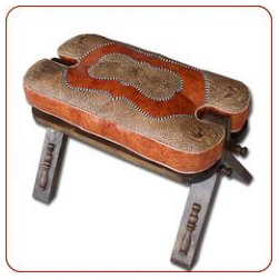"Moroccan camel saddle stool - Camel saddle ottoman made of wood and a hand stamped leather cushion. Measures 23"" long x 16"" high x 16"" wide."
