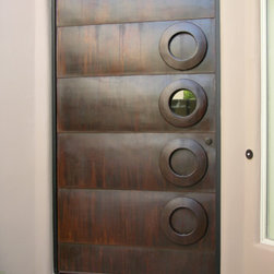 steel door - The window and door handle of this contemporary steel door  with a wood-faced interior are integrated into the design. The entire door pivots beautifully.