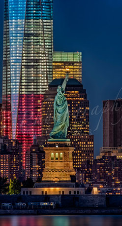 Lady and Freedom - Lady and Freedom ~ New York City Skyline view with Lady liberty and the rising red, white and blue Freedom Tower at twilight. ©Susan Candelario SDC Photography all rights reserved