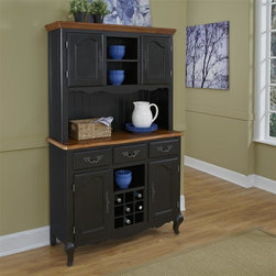 HomeStyles - Oak and Rubbed Black Buffet and Hutch - The buffet and hutch is constructed of hardwood solids and engineered wood in a distressed oak and heavily rubbed black finish. The oak top features several distressing techniques such as worm holes, fly specking, and small indentations. Features include three storage drawers, four storage doors with adjustable shelves, removable wine rack, three center fixed shelves, and cable accessibility through bottom of hutch. Beautifully accented with shaped carved proud legs, corner pegs accents, and detailed brass hardware. Assembly required. 44.5 in. W x 17.5 in. D x 72 in. H
