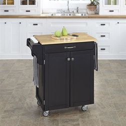 HomeStyles - Kitchen Cart in Black Finish - Prepare your meals easily with this convenient kitchen cart in a beautiful, black finish! Its accessible bottom cabinet features an adjustable shelf for storage and side compartment to store your spices! This will be useful tool in any home! * Wood top in natural finish. Solid wood construction. Utility drawer. Metal drawer slides. Two cabinet doors open to storage with adjustable shelf inside. Handy spice rack. Two towel bars. Heavy duty locking rubber casters for easy mobility and safety. Two of the casters lock. Clear coat finish helping to protect against wear from normal use. Made from Asian hardwood and steel. Made in Thailand. Assembly required. 32.5 in. L x 18.75 in. W x 35.5 in. H