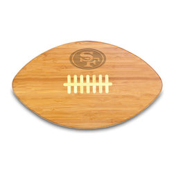 """Picnic Time - San Francisco 49ers Touchdown Pro Cutting Board in Natural Wood - The Touchdown! cutting board is a 15"""" x 8.75"""" x 0.75"""" board made of eco-friendly bamboo with a standard football design, with 123 square inches of cutting surface. It can be used as a cutting board or serving tray, or use both sides of the board, one for cutting and the other for serving. The backside of the board is solid dark bamboo. Go long...for the Touchdown! Decoration: Engraved"""