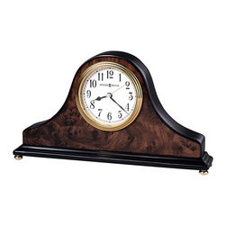 "Howard Miller - Tambour Design Mantel Clock w Decorative Burl - This gracefully curved mantel clock is finished in a dark, attractive walnut color. The sides and base are black, with a swirling wood burl pattern applied to the front and back of the piece. It's elegantly crafted, made to be set on any mantel or shelf for as an elegant statement. Brass legs and accents complete this beautiful clock. * An attractive high-gloss walnut piano finish on a hardwood tambour style table clock featuring a wood burl pattern on the front and back, with black sides and base. . Polished brass button feet. . Polished brass tone waterfall bezel and glass crystal. The off-white dial offers black Arabic numerals, black hour and minute hands, with a brass second hand. . Quartz movement includes 1 AA battery. . 3.25 in. clock face. H. 6"" (15 cm). W. 10-1/2"" (27 cm). D. 2"" (5 cm)"