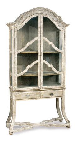 Kathy Kuo Home - Dauphine French Country Antique Beige Display Case Cabinet - The details make all the difference on this inspired antique country cabinet. From its French curved crown to its slender, crisscrossed carved legs and ball feet, Parisian design is evident everywhere. This piece would make a beautiful addition to both a refined dining room or a rustic cottage living space, safely holding everything from your best china to your treasured tomes within its glass clutches.