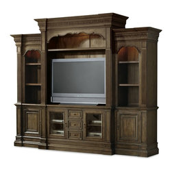 Hooker Furniture - Hooker Furniture Rhapsody 4Pc Entertainment Wall Group - The groundbreaking Rhapsody collection brings together classic design elements, grand scale, and a relaxed rustic finish to create an impassioned marriage of casual opulence. Features: Material: Hardwood Solids, Pecan Veneers, Metal, Seeded Glass, Resin. Style: Traditional. Left Pier: One adjustable wood-framed glass shelf; one adjustable shelf; one door with one adjustable shelf behind; one light controlled by three intensity touch switch; 28 3/4W x 21 1/2D x 93 1/4H. Right Pier: One adjustable wood-framed glass shelf; one adjustable shelf; one door with one adjustable shelf behind; one light controlled by three intensity touch switch; 28 3/4W x 21 1/2D x 93 1/4H. Entertainment Console: Two doors with glass or wood panel option and one adjustable shelf behind each; three drawers with removable dividers for CD/DVD storage; one three plug outlet. Will accommodate most 65-inch and some 70-inch televisions when used alone; 67 3/4W x 24 1/2D x 36 1/2H. Entertainment Console Hutch: One adjustable shelf; two lights controlled by a three-intensity touch switch; 72 1/4W x 26 1/4D x 68 1/4H. TV Space: Inside pilasters and height to shelf in center position: 54 1/2W x 21 1/4D x 42 3/4H; Width inside end panels: 63W; Height to center of carved opening: 55H; Shelf height settings above console: 37 3/4H, 40 1/4H, 42 3/4, 45 1/4H, 47 3/4H. Will accommodate most 55-inch televisions and some 60-inch televisions. Finish: Walnut Colored Rustic Finish.