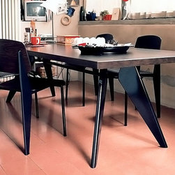 Vitra - Jean Prouv Dining Table - At the beginning of the 1950s Prouv designed the EM Table for the ''Maison Tropique'' project. With every single detail governed by its construction, the table follows the aesthetics of necessity. It illustrates the force vectors and static connections in a way that is otherwise only familiar in the context of civil engineering works. Features: -Crafted of Oak veneers.-Powder coated table top.-Molded sheet steel base.-Design is the process by which almost all objects in Vitra's surroundings are instilled with a specific design and function - from cars to paper clips, from clothing to chairs. And design does not just mean giving things a shape. Design creates the basis which enables things to function in the desired manner. It is a process in which complementary but often mutually contradictory requirements have to be met (comfort, technology, ergonomics, ecology, economics, aesthetics). Design can be successful only when the balance of all these factors is attained..-Once in the factory, Vitra staff manufacture furniture to precise standards, individually ensuring the quality of each product..-Vitra has been certified for DIN EN ISO 9001: 2000..-Vitra's focus on quality does not end at the factory door - they believe that providing clients with exceptional service is just as important as manufacturing furniture. In order to make certain Vitra clients enjoy consistently high quality in all Vitra products, they have set up their own test center which monitors products against criteria that are far more stringent than the statutory standards..-Ergonomics is an applied science that studies the relationship between human beings and machines. Vitra produces furniture that responds to the ergonomic requirements of the body and as a consequence has a positive effect on health and well-being. All Vitra products (except for the experimental series Vitra Edition) have been tested by independent institutions. They comply with prescribed standar