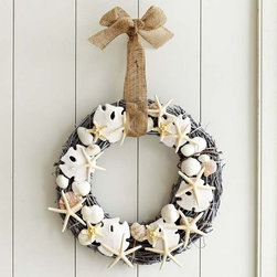 Faux Shell Wreath - A wreath adorned with sand dollars, starfish and assorted shells adds a beachy Christmas touch to a more tropical holiday setting.