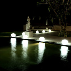 Flat Ball - Portable Outdoor LED Lamp | Smart & Green - Floating delicately on your pool or elegantly placed on land, Flat Ball diffuses a pleasant light to suit your requirements. White light, candle effect or 160,000 colors to choose from… there are so many options for your evening.  Because it can be immersed in up to 2 meters of water and is impact-resistant, this lamp offers many opportunities for fun and is recharged by simply placing it on its charging station.  And if you'd like to change the color or switch it off without getting up from your sofa, use Pebble, the compatible remote control unit that you'll find in the accessories section.