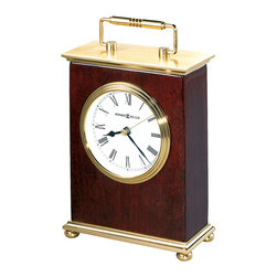 "Howard Miller - Howard Miller - Rosewood Bracket Table Top Cl - Everyone needs a good quality small table top clock for that little space where you need a clock. Brushed brass top and base with polished edges and decorative brass handle make this small wonder a perfect and classic addition. White dial with triple rim, polished brass tone bezel and the touches of class that every clock needs. Finished in Rosewood Hall this gorgeous little clock will fit right in. * Brushed brass top and base with polished edges and decorative brass handle. . White dial with triple rim, polished brass tone bezel. . Finished in Rosewood Hall on select hardwoods and veneers. . Quartz movement includes (1) AA battery. . H. 8-1/4"" (21 cm) . W. 5"" (13 cm). D. 2-1/4"" (6 cm)"