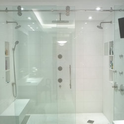 Palm Beach Condo - Sunex supplied the stainless steel and glass custom Kinetik shower enclosure by Fleurco.  Custom his and hers shower with dual showerheads, ceiling shower, body sprays, and handshower with controls located by the door and handshower and body sprays for usability.  We carefully plan with the interior design team and homeowners to create their perfect home spa experience.  Contemporary towel warmer by Myson.  Shower fittings by Watermark.