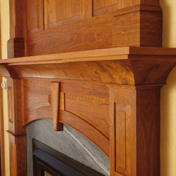 Cherry Mantel - The design of this classic cherry mantel and matching overmantel combine with a striking soapstone surround to become the focal point of the room. The raised panels and center key demonstrate the detailed workmanship.