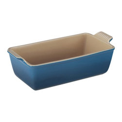 Le Creuset - Le Creuset Heritage Stoneware 1.5 qt. Loaf Pan - Marseille Blue - PG1049-23 59 - Shop for Bread Baking from Hayneedle.com! The first thing your Le Creuset Heritage Stoneware 1.5 qt. Loaf Pan - Marseille Blue bakes up is going to be your famous lemon pound cake. English muffin bread or meatloaf would be great too but the stunning dark blue enamel would make your cake sing. Plus its vintage-inspired design and built-in scalloped handles add charm. Not just a pretty face this loaf pan is made of durable stoneware that provides a perfectly even heat without scorching. It's enamel coating resists scratches and stains and is as tough as it is gorgeous. You can use it in the freezer microwave oven broiler and even the dishwasher. About Le Creuset of America Inc.From its cast iron cookware to its teakettles and mugs Le Creuset is a global standard of inimitable color and quality. Founded in 1925 in the northern French town of Fresnoy-Le-Grand Le Creuset still produces enameled cast iron in its original foundry. Its signature color Flame was modeled after the intense orange hue of molten cast iron within a cauldron (or creuset in French) and has been a Le Creuset bestseller from the company's first year to the present day.Though best known for its vibrantly colored cookware and original inventions such as the Dutch oven Le Creuset has also forged a name as a creator of stoneware mugs and enamel-coated stainless steel teakettles. The style and performance of Le Creuset's Cafe Collection and tea accessories are rooted in classic French cookware: bold colors cylindrical loop handles unmatched thermal resistance and heat distribution and of course the iconic Le Creuset three-ring accent. Through its consistent qualities of authenticity originality and innovation Le Creuset maintains a connection to both heritage and modernity.